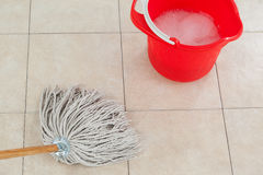 Bucket with foamy water and mopping the tile floor. Red bucket with foamy water and mopping the tile floor Royalty Free Stock Photography