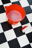 Bucket with foamy water and scrubbing brush. Bucket with foamy water and the brush stands on the floor tessellated. High angle view Stock Photography