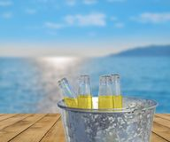 Bucket with four bottle of refreshment drink on wooden terrace. With blue sea background Royalty Free Stock Photography