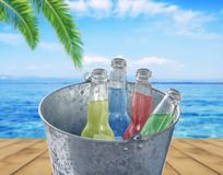 Bucket with four bottle of refreshment drink at wooden terrace. With sea background Stock Photo