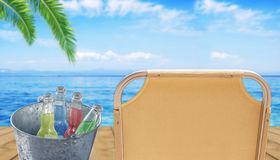 Bucket with four bottle of refreshment drink at wooden terrace. With sunbed and blue sea background Royalty Free Stock Image