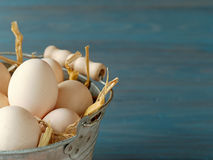 Bucket of fresh eggs. Organic eggs from own chickens in traditional iron bucket with straw inside Royalty Free Stock Photos