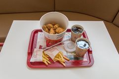 Bucket of fried chicken hot wings, french fries, two cup with pepsi for drink and ketchup in KFC Kentucky Fried Chicken fast foo. Gdansk, Poland - February 28 royalty free stock image
