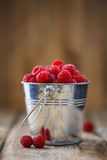 Bucket full of freshly picked raspberries. On wooden table with space for text Stock Photos