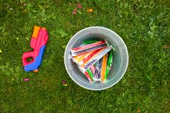 A bucket full of popsicles and a water gun on the grass