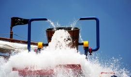 Bucket of fun. Bucket full of water dumping down on families below stock image
