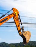 Bucket ground excavator with electrical messy wire cables. royalty free stock images