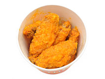 Bucket of hot wings. Bucket of spicy hot wings in isolated white background royalty free stock photo