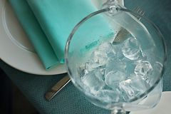 Bucket of ice and tongs on a serving table. With a plate and a napkin Stock Photography