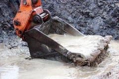 bucket les scoops arrosent hors d'un fossé sur le site pour la construction la route après forte pluie Photographie stock