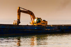 Bucket Loader In Vessel On Riprap Works Royalty Free Stock Photos