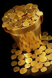 Bucket of Money. Bucket of golden coins, with black background and warm lighting Royalty Free Stock Photo