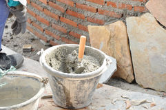 Bucket of mortar with trowel beside constructing brick wall Stock Image