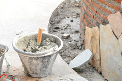 Bucket of mortar with trowel beside constructing brick wall Stock Photo