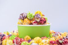 bucket of multi-colored popcorn stands in a pile of cereal, on a white background stock images