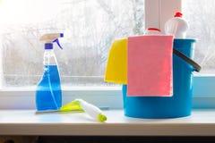 Bucket o pulverizador e o rodo de borracha para a limpeza de janela no peitoril da janela foto de stock