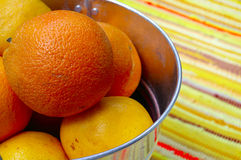A bucket of oranges. A bright bucket of oranges and grapefruits on striped colorful textile background stock images