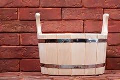 Bucket para un baño en una superficie del ladrillo. Imagen de archivo libre de regalías