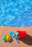 Bucket with plastic beach toys  near pool Stock Photography