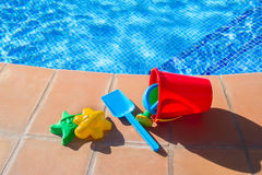 Bucket with plastic beach toys  near pool Stock Photo