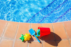 Bucket with plastic beach toys  near pool Royalty Free Stock Photography