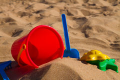Bucket with plastic beach toys in sand Stock Images