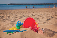 Bucket with plastic beach toys in sand Stock Photo