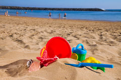 Bucket with plastic beach toys in sand on sea Royalty Free Stock Photos