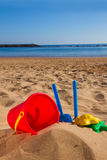 Bucket with plastic beach toys in sand on sea shore Royalty Free Stock Photo