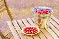 Bucket and a plate with cherries on the table Stock Photography