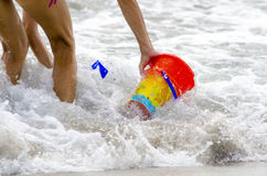 Bucket and play for baby washed by the sea with arms and legs. Bucket and play for baby washed by the sea in summer stock photos