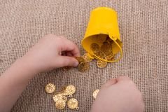 Bucket and plenty of fake gold coins on canvas royalty free stock photos