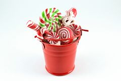 Bucket of Presents. A souvenir for Christmas. Nice little present looking like a red coloured bucket full of sweets. Sweets are lollipops striped in red, white Royalty Free Stock Photo