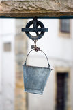 Bucket and pulley. Metallic bucket in the sheave of the curbstone of an artesian well Stock Photo