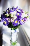 A Bucket of purple flowers. Standing near the window Royalty Free Stock Photo