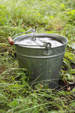 Bucket with rainwater. In grass Royalty Free Stock Photo