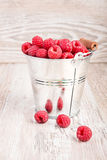 Bucket of raspberries. Shiny bucket of fresh tasty raspberries on wooden table Stock Photography
