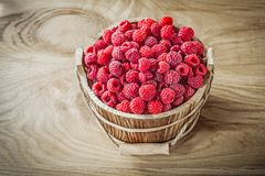 Bucket with raspberries on wooden board.  Royalty Free Stock Images