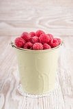 Bucket of raspberries on wooden table. Bucket of fresh tasty raspberries on wooden table Royalty Free Stock Photography