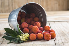 Bucket with ripe arbutus unedo fruits. Leaves and flowers on a wooden background Stock Photography