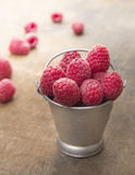 Bucket of ripe raspberries on wooden table Royalty Free Stock Photo