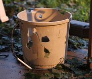 Bucket ruined by hail storm Stock Images
