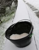 Bucket with salt used to melt ice and snow. Black bucket with salt used to melt ice and snow from the sidewalk after the snowfall stock photography