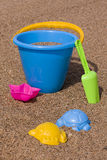 Bucket on sand. Blue bucket with a multicoloured toys on the sand royalty free stock photos