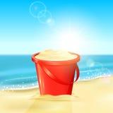 Bucket of sand on beach Stock Photos