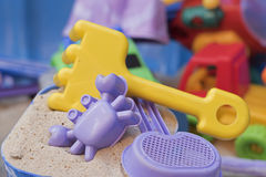 Sandpit. A bucket with sand, a crab shaped sand mould, a sieve and a yellow fork, with other toys in the background Stock Images