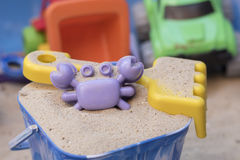 Sandpit. A bucket with sand, a crab shaped sand mould and a yellow fork, with other toys in the background Stock Photography