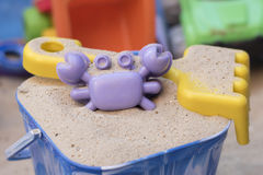Sandpit. A bucket with sand, a crab shaped sand mould and a yellow fork, with other toys in the background Stock Image
