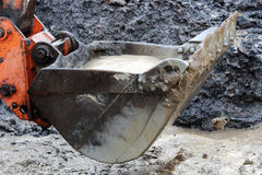 bucket scoops water out of a ditch on the site for the construction  the road after  heavy rain Royalty Free Stock Image