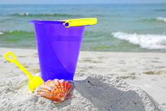 Bucket and seashell on beach. Purple pail and pretty seashell in sand by ocean royalty free stock photos
